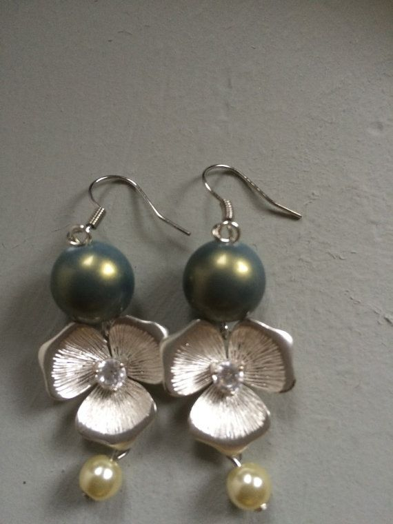 Deze oorbellen hebben een luxe uitstraling. Ze bestaan uit: groene glasparels met metallic glans, zilveren bloemhangertjes met een swarovskisteentje en onderaan hangt een crème kleurig glaspareltje. Van elk ontwerp maak ik er maar 1. Dat maakt ieder sieraad uniek.  Mocht u nog vragen hebben, dan hoor ik het graag.