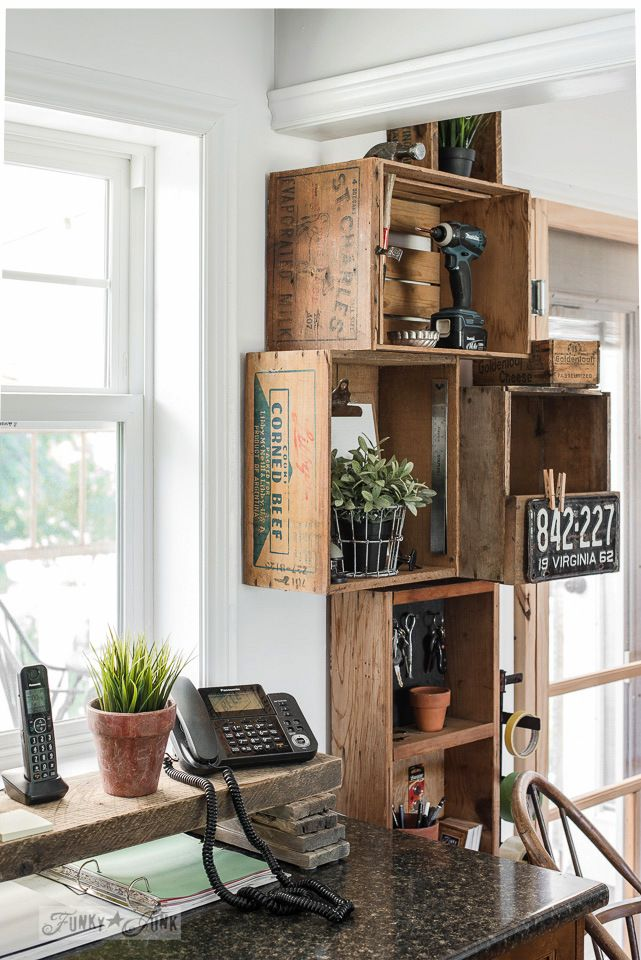 Stacked vintage crates and a reclaimed wood shelf for a rustic kitchen phone station against white walls.   funkyjunkinteriors.net