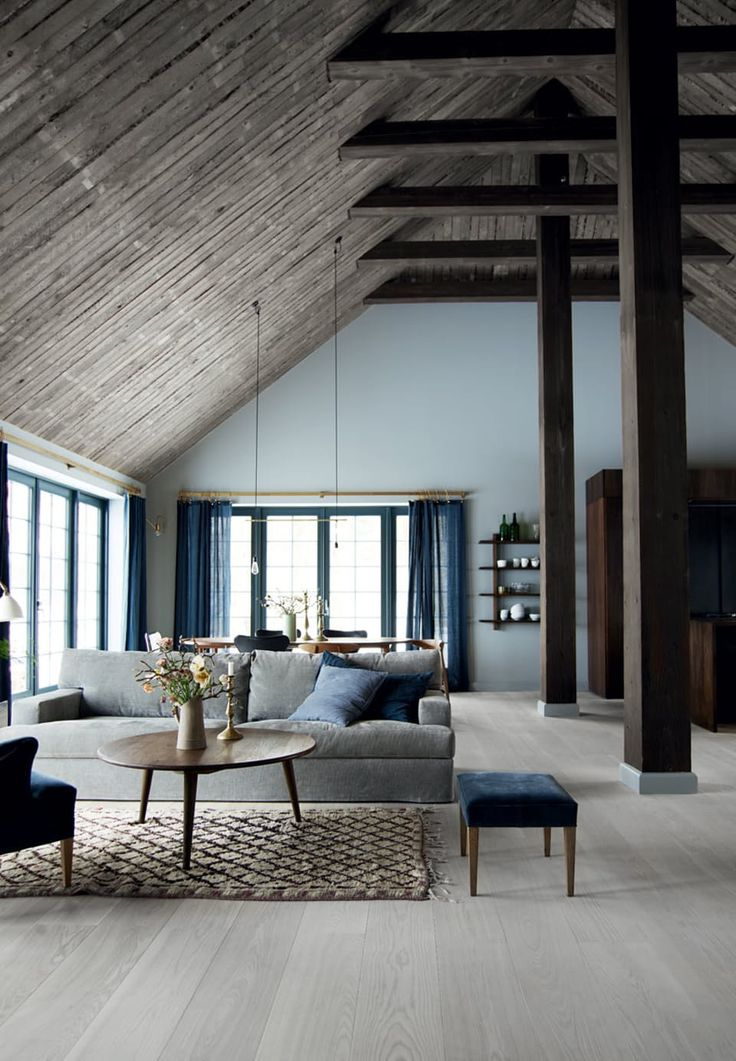Nordic living room with blue, grey and wooden tones. The high ceiling makes the room appear very large and with spacious.