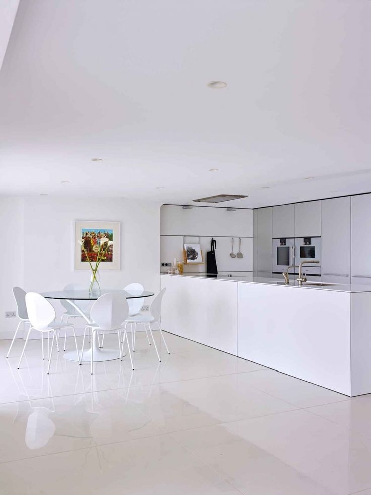 Minimalist White Kitchen With Italian Round Glass Dining Table And White Dining Chairs Kitchen