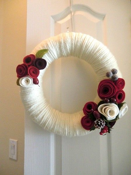 Honor a special person with a spectacular wreath of deep red and cream felt roses, bright red berries and frosted pine cones on a creamy, off-white