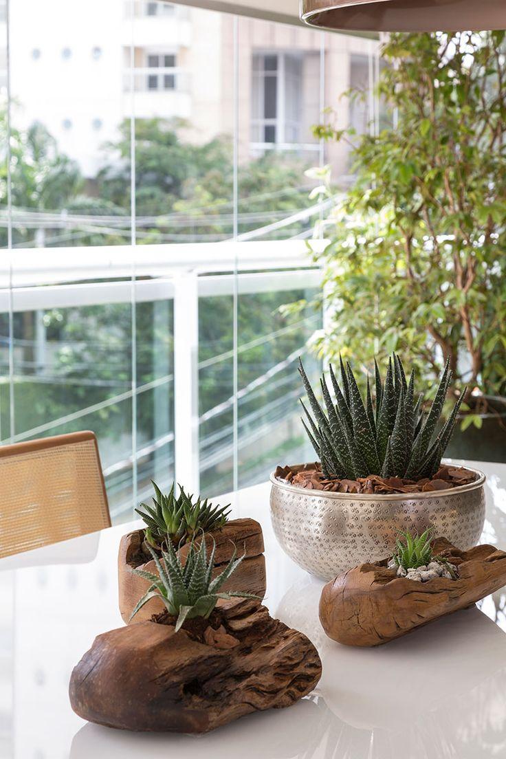 Decoração de apartamento moderno e integrado. Detalhes da decoração da mesa de jantar retangular branca, com vaso de planta, adornos e luz natural.