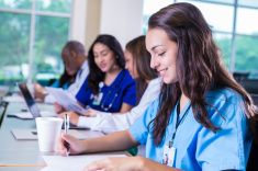 Happy young nursing student taking notes during college class stock photo