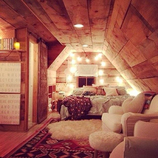 Attic room. Wood, fur, fairy lights, cozy furniture and piles of blankets, pillows and rugs.
