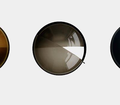 La lampe Shade porte bien son nom, on peut ajuster sa couleur et son intensité lumineuse avec de l'ombre. Cette lampe de paroi sphérique est l'oeuvre de Johansen Faurschou.  Couleur et lumière sont déterminées par l'une des deux teintes qui se chevauchent, il suffit de la tourner. La lampe se compose de 2 teintes de verre dans un cadre métallique mince. L'ombre intérieure est fixe et les diapositives d'ombrage extérieures tournent, soit pour couvrir la lumière soit pour la laisser sortir