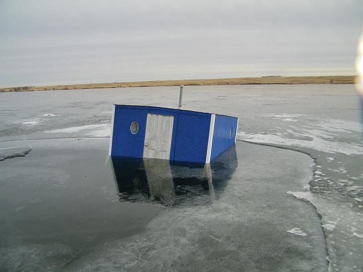 Ice fishing house fish house frozen in ice ice fishing for Ice fish house