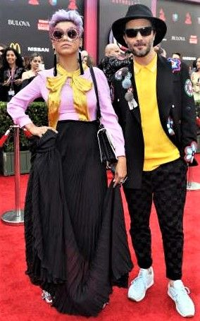 2017 Latin Grammy Awards: Fashion hits and misses - November 14, 2017:  Well. They get points for successfully color-coordinating without looking too matchy-matchy! Bomba Estereo singer Liliana Saumet paired a pink long-sleeve blouse with a marigold bow tied at the neck with a pleated black maxi skirt, pink shades and black fringe earrings. Her bandmate, group founder Simon Mejia, wore a marigold button-down with checkered black pants, a black fedora and a black jacket featuring...