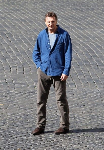 """Liam Neeson Photos Photos - Liam Neeson and Olivia Wilde film scenes on the set of writer/ director Paul Haggis's new movie """"Third Person,"""" in Farnese Square in Rome. In Neeson's scene, he kneels in front of a child that sits on a fountain and talks to him. Wilde wears a form fitting white dress and gets a kiss on the cheek from Neeson. - Olivia Wilde and Liam Neeson Film in Rome"""