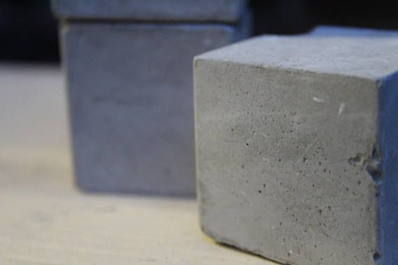 Four concrete building blocks. Can be used as paperweights, decoration, display purposes. I personally use them to put tea light candles on. Gives them a modern brutalist feel. Each cube is individual and all slightly different. You can see from the picture even though all four are from