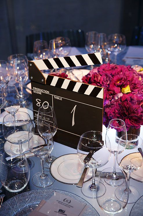 A clapperboard is a unique table number for film-loving couples.