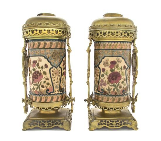A Pair of Zsolnay Gilt Bronze and Brass Mounted Fluid Lamp Bases,  each decorated in the Aesthetic taste, the ceramic cylindrical body decorated with continuous stylized floral bands, set within foliate and dragon cast mounts, the brass font stamped Messengers Patent, the ceramic body with Zsolnay Pecs mark, further numbered 11.  Height 14 1/4 inches. 11/1125U
