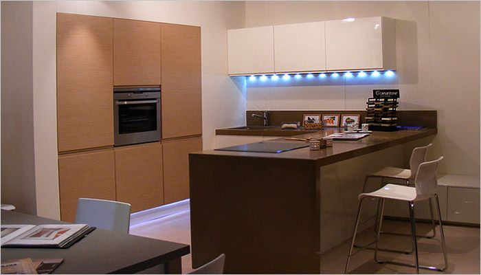 Moderne keuken met bruine kleuren - houtstructuur in de ingebouwde keukenkasten en indirecte verlichting