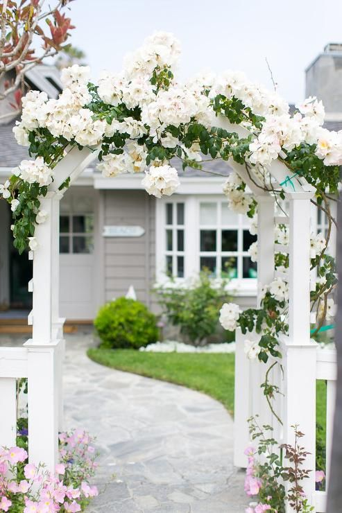 A winding stone pathway flanked by a white picket fence leads through a flower covered front gate arbor.