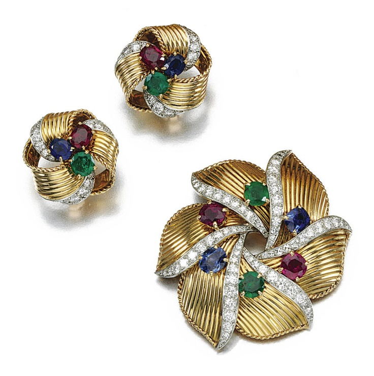 GEM-SET AND DIAMOND DEMI-PARURE, CARTIER, 1950S. Comprising: a brooch and a pair of ear clips en suite, set with cushion-shaped and circular-cut emeralds, rubies and sapphires accented with brilliant- and single-cut diamonds, signed Cartier Paris and numbered, French assay and maker's marks to each piece.