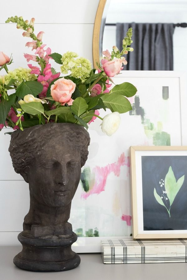 Simple dresser vignette with planter statue, decorative box, and two pieces of layered art