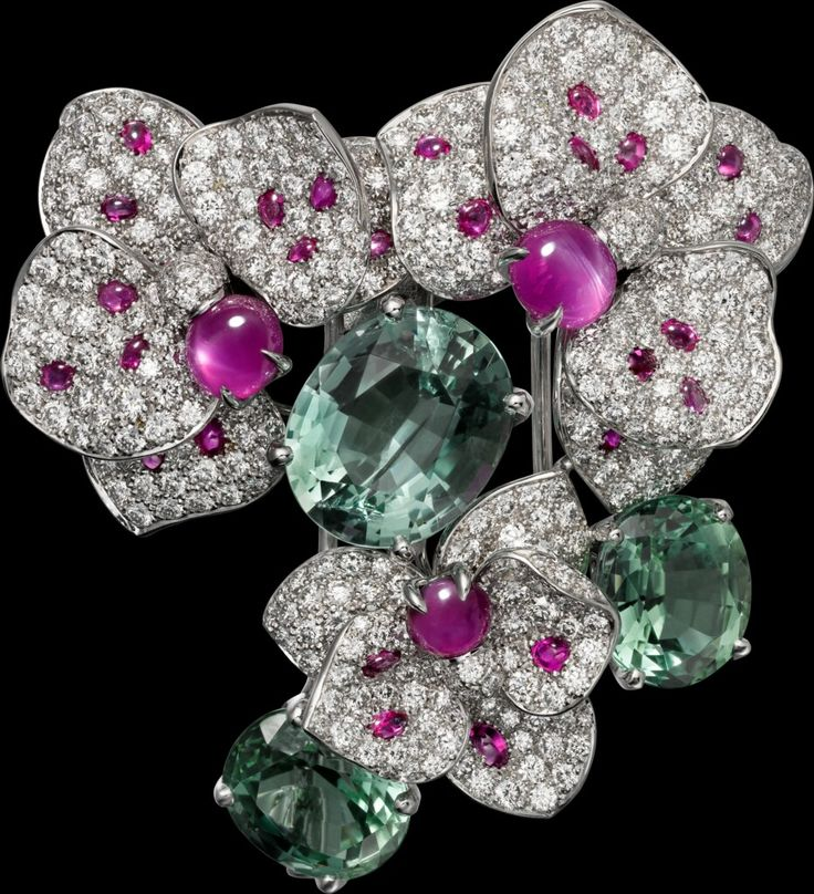 "CARTIER. ""Disa"" Brooch - white gold, one 5,60-carat oval-shaped green beryl, two oval-shaped green tourmalines totaling 7,62 carats, three cabochon-cut star pink rubies from Burma totaling 3,75 carats, cabochon-cut rubies, brilliant-cut diamonds."