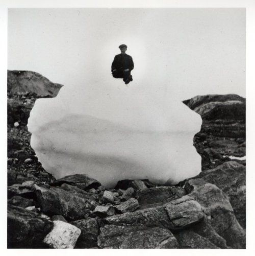 """The caption reads:""""View of a person sitting on a large ball of snow on rocky ground."""""""