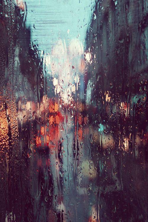 Photographie. Derrière la vitre ruisselante, la ville et ses lumières sous la pluie.