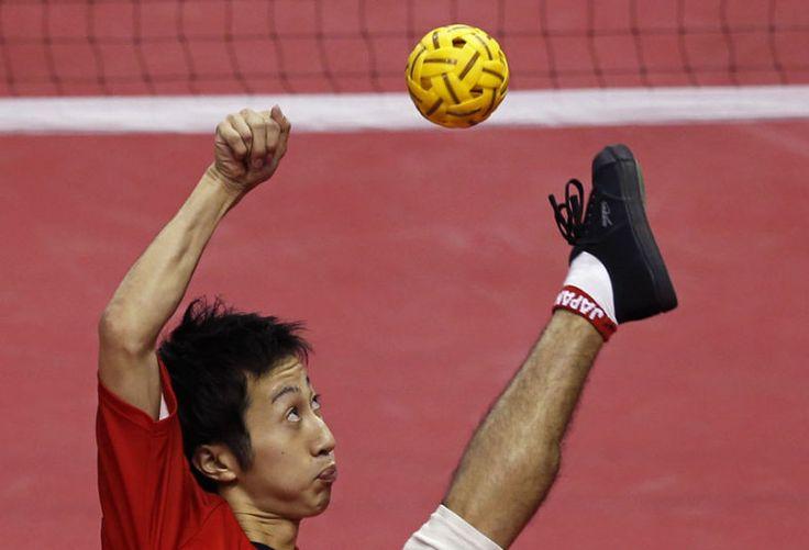 Japan's Masayuki Ishizuka strikes the ball against South Korea during their men's team sepaktakraw game at the Bucheon Gymnasium during the 17th Asian Games in Incheon