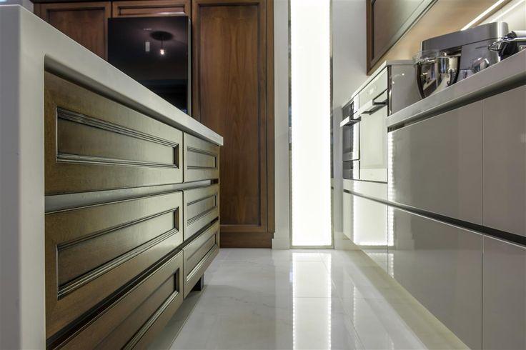 Μοντέρνα κουζίνα με ντουλάπια από λευκό ακρυλικό με ενσωματωμένες χούφτες στο κάτω μέρος και από καρυδιά στο επάνω. Κεντρικά υπάρχει νησίδα και τραπέζι κουζίνας.