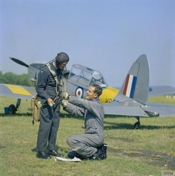 An Aircraft Apprentice has his parachuite harness adjusted by a Flying Instructor standing in front of a De Havilland Chipmunk T.10 aircraft prior to an 'air experience' flight at the Royal Air Force No 1 School of Technical Training at RAF Halton, Buckinghamshire.