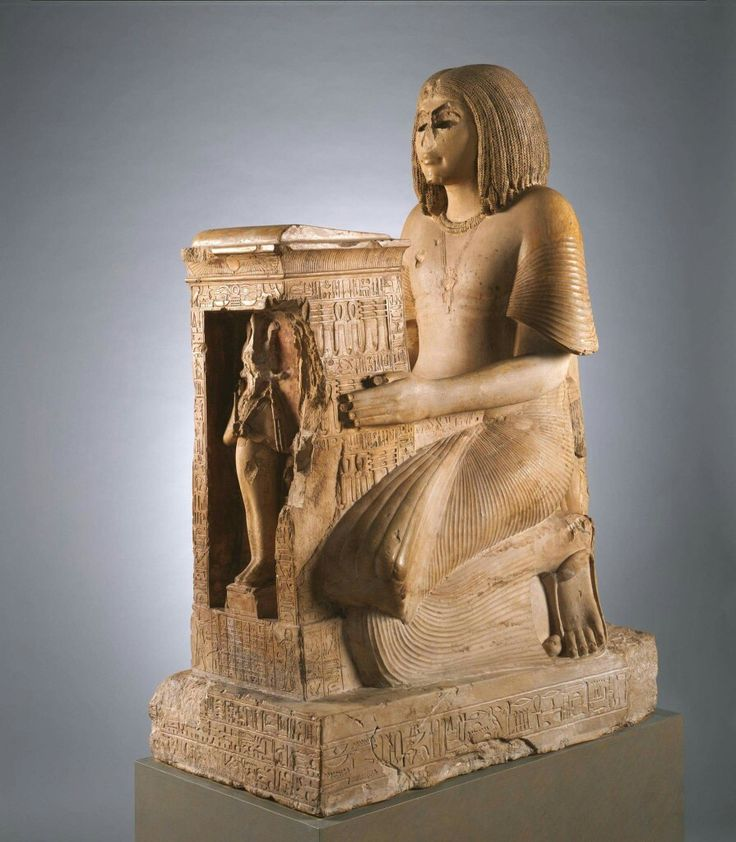 Kneeling Statue of Yuny 19th Dynasty,reign of Seti I c.a. 1294–1279 B.C. Middle Egypt, Asyut (Lykopolis),Tomb of Amenhotep,Necropolis Cliff tomb,Medjdeni,Khashaba excavations in 1913. Yuny,shown kneeling is dressed in the robe,wig and sandals of a nobleman.His eyes and eye-brows,originally made as inlays, are now lost.Between his knees and outstretched arms he holds a shrine with a figure of the god Osiris.This is one of two statues of Yuny found in or near the tomb.