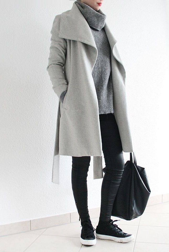 Light grey coat with a darker grey turtlneck shirt. Black leather pants. Black sneakers with a white bottom.