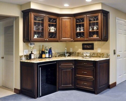 Beautiful little bar in the corner. Great use of space and to showcase glassware. Love those cabinets!