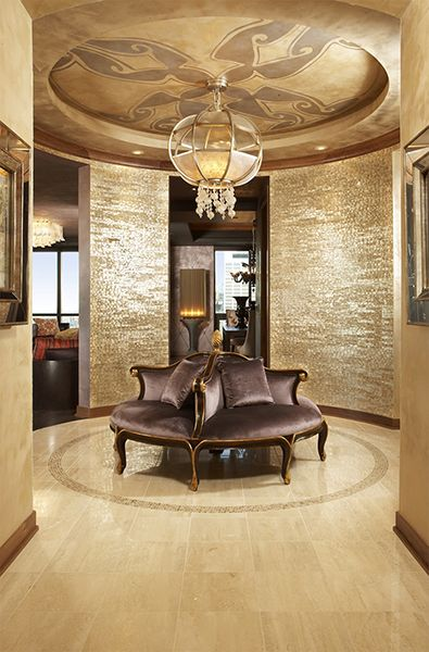 Custom travertine floor design, mother of pearl wall tiles and custom ceiling mural sets the tone for the foyer circular settee.