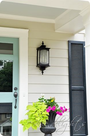 Exterior Curb Appeal: blue door, black shutters, iron planter, blue painted ceiling.