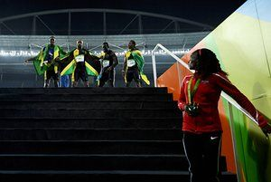 Women's 5,000m silver medalist Hellen Obiri of Kenya looks on as Bolt, Asafa Powell, Yohan Blake and Nickel Ashmeade of Jamaica pose with their gold medals
