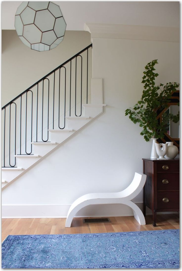 love the lines of the stair railing with that modern pendant.