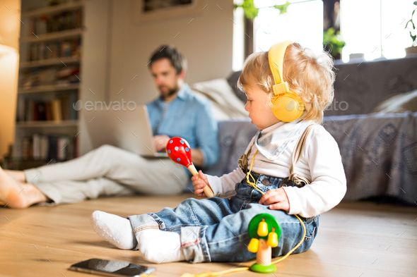 Father And Son With Smartphone Earphones And Laptop By Halfpoint Young Father At Home Sitting On Wooden Floor Father And Son Young Fathers Technology Photos