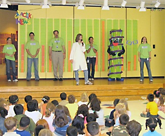 Felix the Helix (second from r, and really NHGRI's Melissa Meredith) joins a genome institute cast onstage at the Oyster Bilingual School cafeteria. The ensemble taught kids about science and DNA.