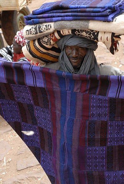 Africa | Travelling along the Niger River in Mali; Vendor holding up a handwoven wood, indigo dyed blanket. | ©African Desert Craft: