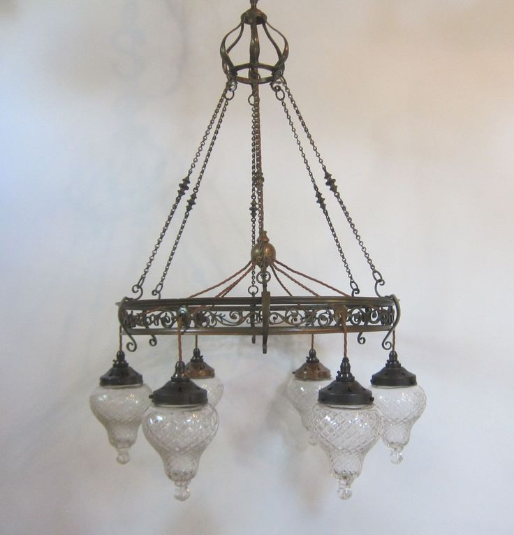 English six arm ceiling light with a Gothic feel and in the original patinated brass finish, further complemented by teardrop style shades. www.antiquelightingcompany.com