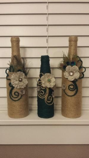 Set of 3 jute twine wrapped wine bottles. Beautiful modern decoration touch on them. Fabric flowers. Peacock feathers. Perfect for home by lorrie