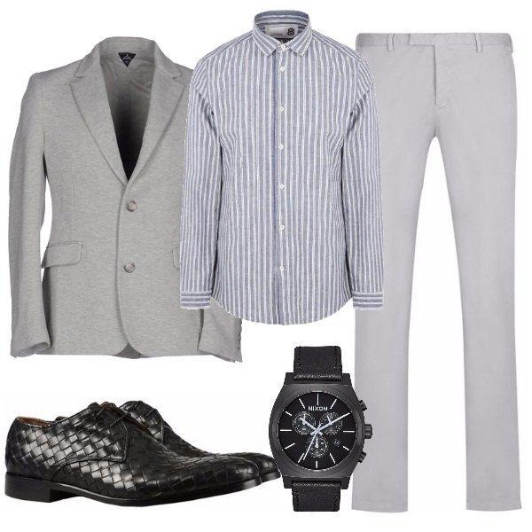 Per l'ufficio o per una serata informale il completo grigio, la giacca in cotone due bottoni, i pantaloni lineari, la camicia in tela a righe, danno un allure singolare le stringate di pelle e l'orologio nero.
