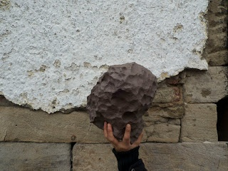 Bianca Hester, situated upon the surface of the earth, a series of actions occurring in Glasgow, developed for the Common Guild for the Glasgow Internaitonal Festival of Visual Arts, 2012    Cast Meteorite held aloft in a series of locations     A cast polyurethene copy of a Henbury iron meteorite from   the Northern Territory of Australia, held aloft in front of   various walls and facades in Glasgow.  photos: Chris Dyson