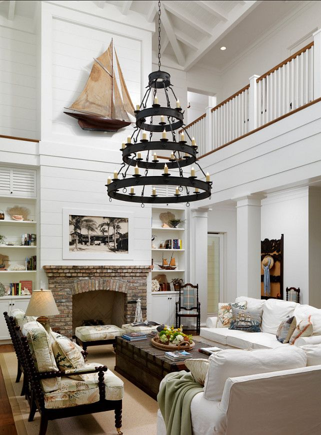 family room with beachy cottage feel: horizontal plank walls, coastal/nautical accent pieces, bright and airy.