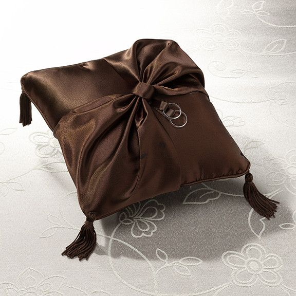 """Measuring 8"""", this brown satin ring bearer pillow is decorated with a large brown bow. A pair of silver rings hang from brown ribbon coming off the knot of the bow. Brown tassels are at each corner of"""