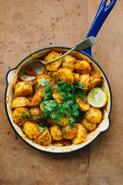 POTATO CURRY == Serves 4-6 with rice or more as part of a larger meal == 1kg small potatoes 2 large tomatoes 2 cloves garlic 1t finely grated ginger 2T ghee or olive oil 2t whole cumin seeds 2t mustard seeds  1/2 large onion 2t ground coriander 1t ground turmeric 1 teaspoon garam masala 1/2 teaspoon fine sea salt, or to taste 2 good pinches of unrefined raw sugar a pinch dried chilli flakes, optional the juice of 1/2 lemon fresh coriander and dill leaves, roughly torn, to serve ====