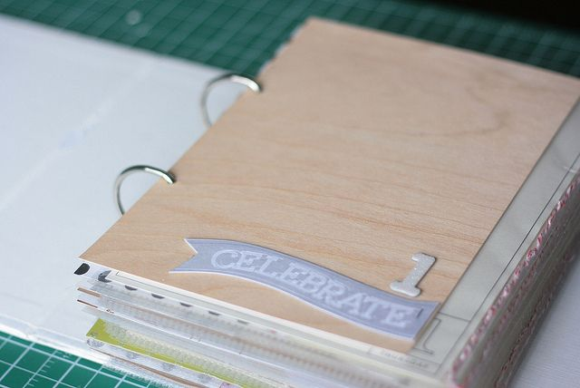 """wood panel page and """"celebrate"""" tag stapled glitter # 1."""