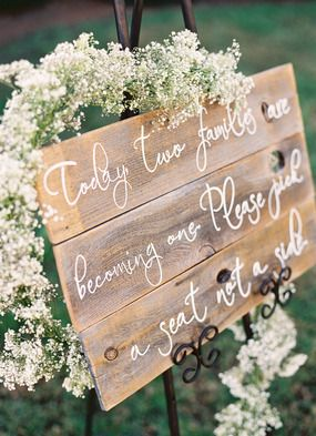 Rustic wood with white lettering, framed by baby's breath...great wedding sign.