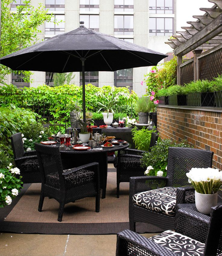 White Flower Bouquet Between Black Wicker Patio Furniture Closed To Black Patio  Umbrella.