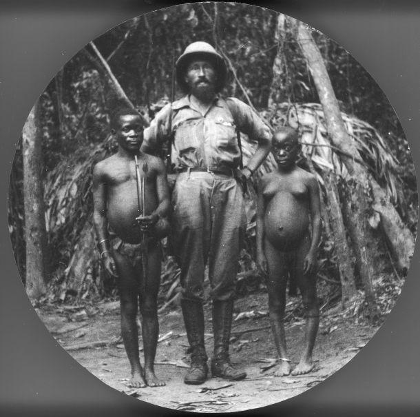 Podróżnik Kazimierz Nowak w Lesie Równikowym Ituri z członkami plemienia Mbuti (charakteryzują się niskim wzrostem). Według opisu redakcji jest to fotografia wykonana przez Kazimierza Nowaka w trakcie jego podróży przez Afrykę. Uganda, 1937 rok.