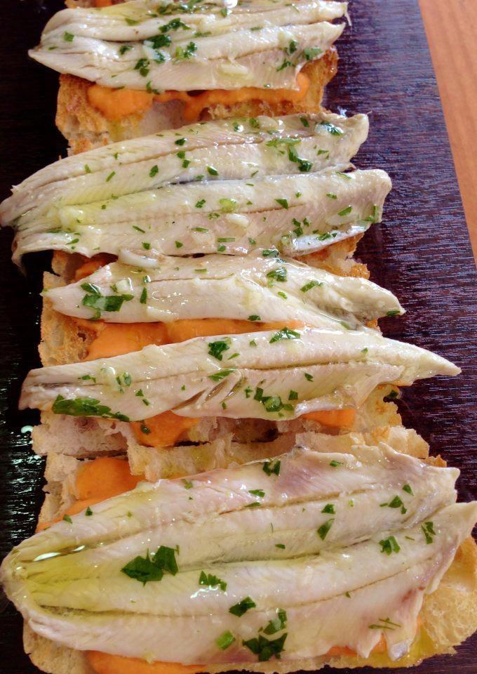 Pan de cristal con salmorejo y anchoas en vinagre.