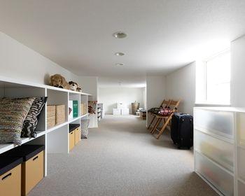 白を基調に壁紙や棚をそろえると、清潔感がでます。1つ1つの棚が大きいのでクッションや、大きめのかごも入るのですっきりとした印象の屋根裏部屋になります。 スーツケースや子供用のチェアも置き方次第でインテリア風に見えてきますね。