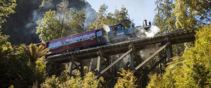 A steam train crosses a historic wooden trestle bridge in the rainforest along the West Coast Wilderness Railway on Tasmania's wild West Coast