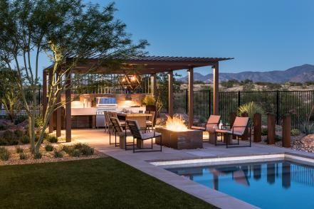 Contemporary and Southwestern styles easily blend in this outdoor space by Kathryn Prideaux. A slatted pergola over the kitchen and seating area offers some shade from the hot desert climate, while a sleek pool encourages a leisurely swim against the mountains.